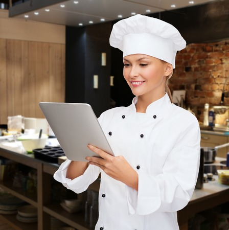 Photo for cooking, people, technology and food concept - smiling female chef, cook or baker with tablet pc computer over restaurant kitchen background - Royalty Free Image