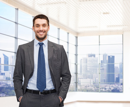 Foto de business, people and office concept - happy young businessman over office room or new apartment background - Imagen libre de derechos