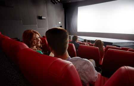Photo for cinema, entertainment, communication and people concept - happy couple of friends watching movie and talking in theater from back - Royalty Free Image