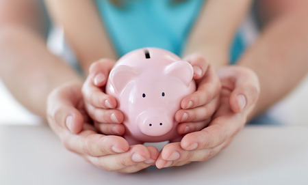 Photo pour family, children, money, investments and people concept - close up of father and daughter hands holding pink piggy bank - image libre de droit