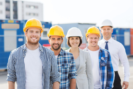 Foto de business, building, teamwork and people concept - group of smiling builders in hardhats outdoors - Imagen libre de derechos