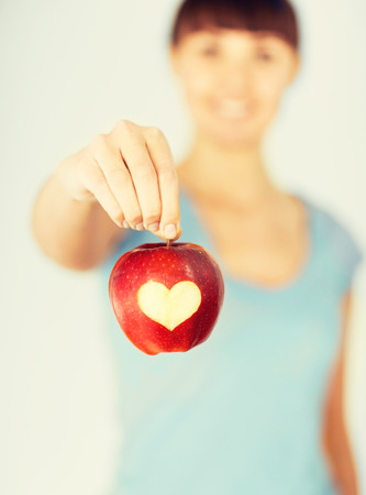 Photo pour healthy food and lifestyle - woman hand holding red apple with heart shape - image libre de droit