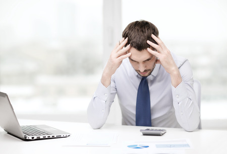 Foto de office, business, technology, finances and internet concept - stressed businessman with laptop computer and documents at office - Imagen libre de derechos