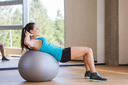 Photo pour fitness, sport, training and people concept - smiling woman flexing abdominal muscles with exercise ball in gym - image libre de droit