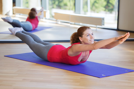 Photo pour fitness, sport, training and people concept - smiling woman doing back extension exercise on mat in gym - image libre de droit