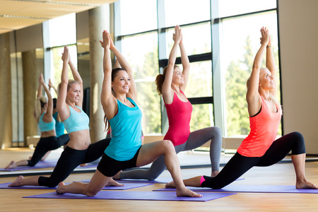 Photo for fitness, sport, training and lifestyle concept - group of smiling women stretching in gym - Royalty Free Image
