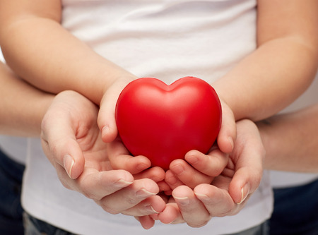 Foto de people, charity, family and advertisement concept - close up of woman and girl holding  red heart shape in cupped hands - Imagen libre de derechos