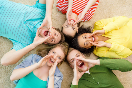 Foto de education and happiness concept - group of young smiling people lying down on floor in circle screaming and shouting - Imagen libre de derechos