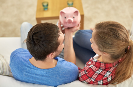 Photo pour money, home, finance and relationships concept - close up of couple with piggy bank sitting on sofa - image libre de droit