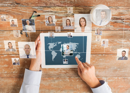 Photo for business, people, international communication, headhunting and technology concept - close up of hands pointing finger to tablet pc computer screen with world map and internet contacts network on table - Royalty Free Image