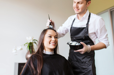 Photo for beauty and people concept - happy young woman with hairdresser coloring hair at salon - Royalty Free Image
