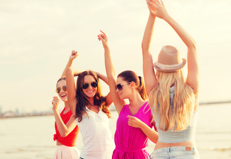summer vacation, holidays, travel and people concept - group of smiling young women in sunglasses and casual clothes dancing on beach