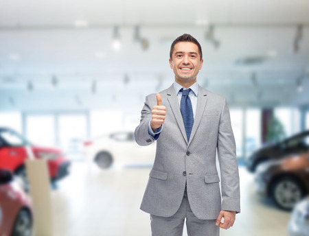 Photo pour auto business, car sale, consumerism, gesture and people concept - happy man showing thumbs up over auto show or salon background - image libre de droit