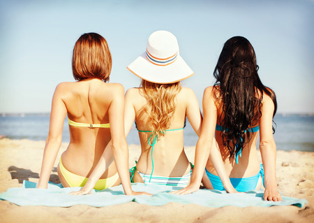 Foto de summer holidays and vacation - girls sunbathing on the beach - Imagen libre de derechos
