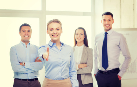 Foto per business and office concept - smiling beautiful businesswoman ready for handshake with team in office - Immagine Royalty Free