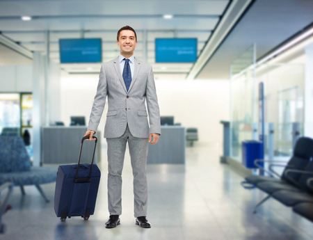 Foto de business trip, traveling, luggage and people concept - happy businessman in suit with travel bag over airport background - Imagen libre de derechos