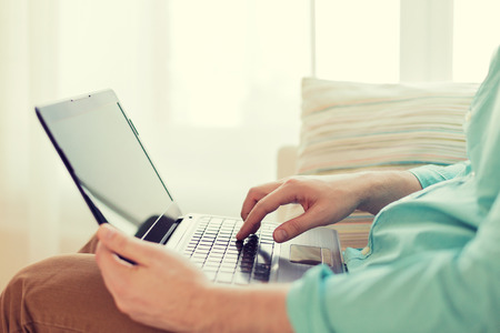 Photo pour technology, home and lifestyle concept - close up of man working with laptop computer and sitting on sofa at home - image libre de droit