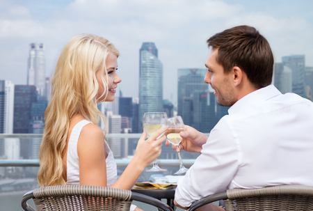 Photo pour summer holidays, people, honeymoon, vacation and dating concept - couple drinking wine in cafe over city background - image libre de droit
