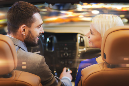 Photo pour love, luxury, nightlife, automobile  and people concept - happy couple driving in cabriolet car over night city lights background - image libre de droit