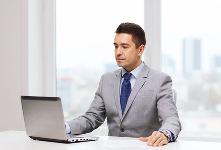 Photo pour business, people and technology concept - smiling businessman in suit working with laptop computer in office - image libre de droit