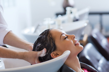Photo pour beauty and people concept - happy young woman with hairdresser washing head at hair salon - image libre de droit