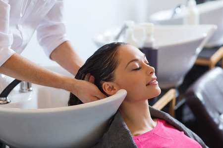 Foto de beauty and people concept - happy young woman with hairdresser washing head at hair salon - Imagen libre de derechos