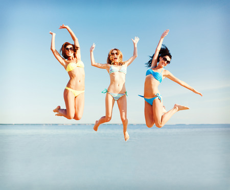 Photo for summer holidays and vacation - girls jumping on the beach - Royalty Free Image
