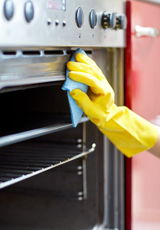 Photo pour people, housework and housekeeping concept - close up of woman hand in protective glove with rag cleaning oven at home kitchen - image libre de droit
