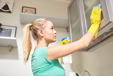 Photo pour people, housework and housekeeping concept - happy woman cleaning cabinet with rag and cleanser at home kitchen - image libre de droit