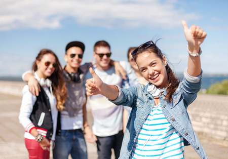 Photo for summer holidays and teenage concept - teenage girl in sunglasses and headphones hanging out with friends outside and showing thumbs up - Royalty Free Image
