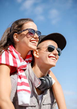 Photo for summer holidays, relationships and teenage concept - smiling teenagers in sunglasses having fun outside - Royalty Free Image