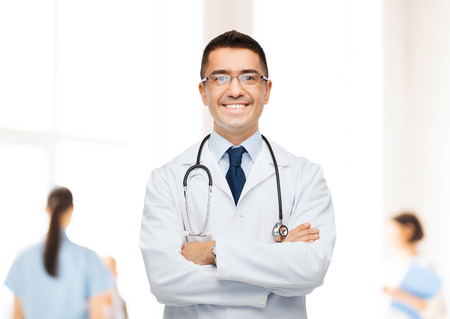 Photo pour healthcare, profession, people and medicine concept - smiling male doctor in white coat over group of medics at hospital background - image libre de droit