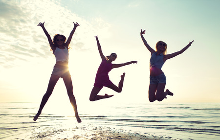 Foto de friendship, summer vacation, freedom, happiness and people concept - group of happy female friends dancing and jumping on beach - Imagen libre de derechos