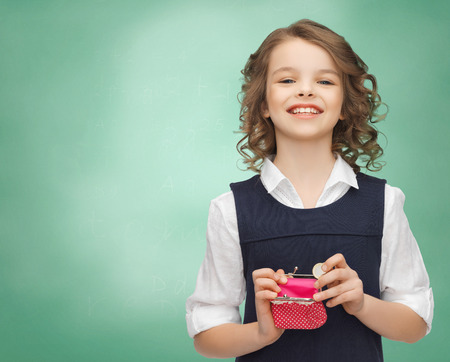 Foto de finances, childhood, people, money and savings concept - happy little girl with purse and euro coin over over green chalk board background - Imagen libre de derechos