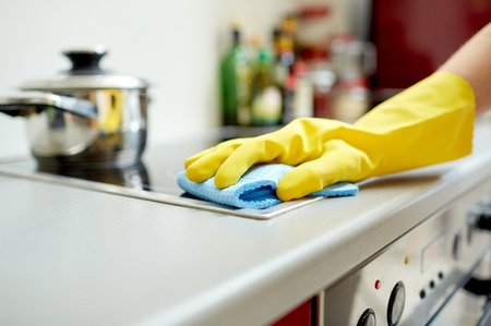 Foto de people, housework and housekeeping concept - close up of woman hand in protective glove with rag cleaning cooker at home kitchen - Imagen libre de derechos