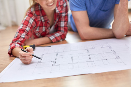 Photo pour repair, building, renovation and people concept - close up of happy couple looking at blueprint at home - image libre de droit