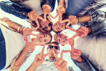 Photo for summer holidays and teenage concept - group of teenagers showing peace or victory gesture - Royalty Free Image