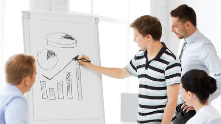 Foto de smiling business team working with flipchart in office - Imagen libre de derechos