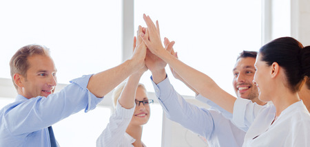 Foto per success and winning concept - happy business team giving high five in office - Immagine Royalty Free