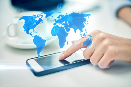 Foto de business, technology, global communication and people concept - close up of woman hand with smartphone and coffee pointing finger to screen over world map projection - Imagen libre de derechos