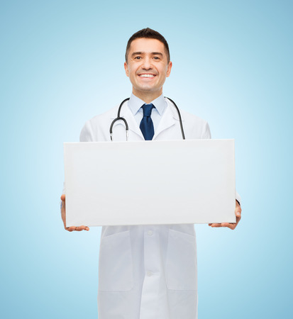 Photo for healthcare, advertisement, people and medicine concept - smiling male doctor in white coat holding white blank board over blue background - Royalty Free Image
