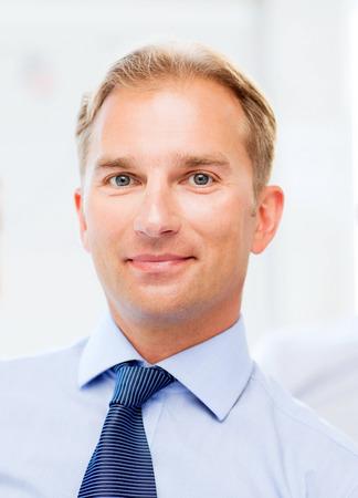 Foto de picture of smiling handsome businessman in office - Imagen libre de derechos