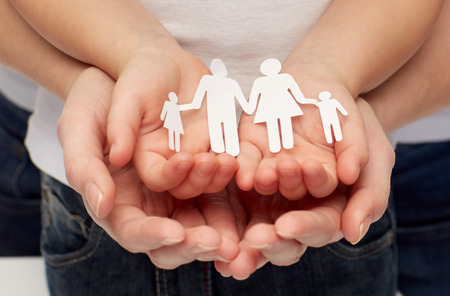 Photo pour people, charity, family and care concept - close up of woman and girl hands holding paper family cutout - image libre de droit