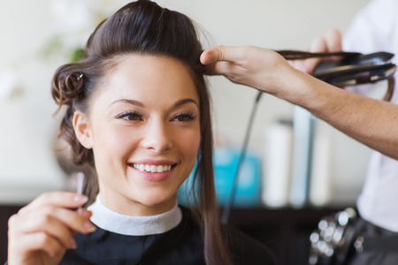 Foto de beauty, hairstyle and people concept - happy young woman and hairdresser with hair iron making hairdo at hair salon - Imagen libre de derechos