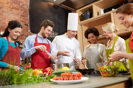 Photo for cooking class, culinary, food and people concept - happy group of friends and male chef cook cooking in kitchen - Royalty Free Image