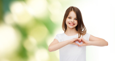 Photo pour advertising, childhood, ecology, charity and people - smiling little girl in white t-shirt making heart-shape gesture over green background - image libre de droit