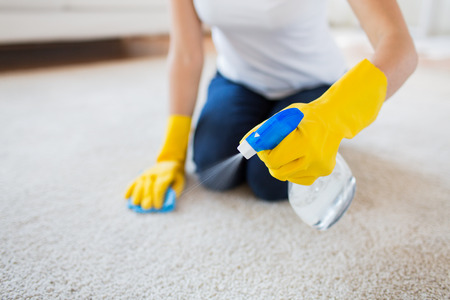 Photo pour people, housework and housekeeping concept - close up of woman in rubber gloves with cloth and derergent spray cleaning carpet at home - image libre de droit