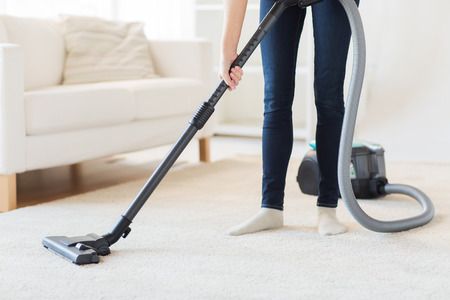 Photo pour people, housework and housekeeping concept - close up of woman with legs vacuum cleaner cleaning carpet at home - image libre de droit