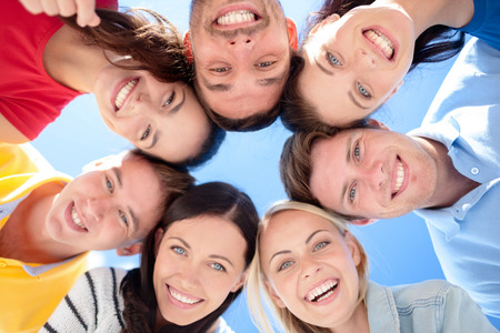 Photo for friendship, summer vacation, holidays and people concept - group of smiling friends standing in circle over blue sky - Royalty Free Image