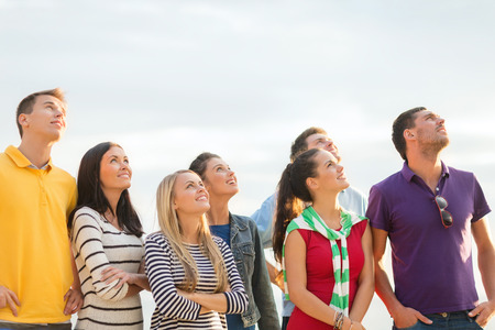 Photo for summer holidays, vacation and people concept - group of happy friends looking up on beach - Royalty Free Image
